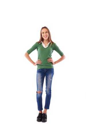 charming girl: Happy charming girl with hands on hips in the studio over white background. Full-length portrait of casual girl wearing white blouse underneath fitted dark olive green sweater Stock Photo