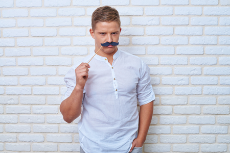 Mid shot of handsome boy frowning when wearing black paper moustache on stick. Looking at camera and smiling while standing with one hand in pocket on a white brick wall background Reklamní fotografie