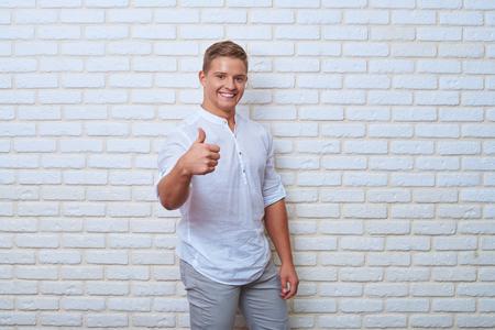 comunicacion no verbal: Mediados de tiro de hombre joven confía en dar la autorización del gesto mientras está de pie contra la pared de ladrillo blanco. Forma de comunicación no verbal