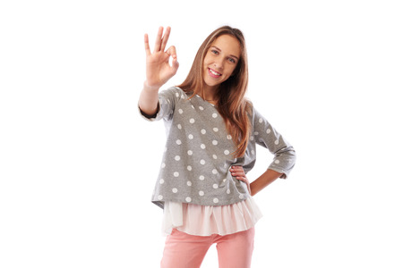 Mid shot of beautiful young girl in trendy casual clothes showing ok gesture against white background. Girl is very happy