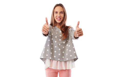 dimple: Mid shot of good-looking girl who is giving two thumbs up while standing over white background, isolated in studio. The thumbs up is positive gesture