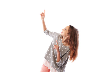 dimple: Mid-length shot of excited girl pointing to the cope space. She kneels down, and pointing upward. Posing in studio isolated over white background Stock Photo