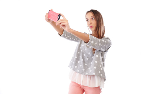 Mid shot of smiling young girl making selfie photo and puckering lips at the camera isolated on a white background. Puckered-up pose shows off flirty side