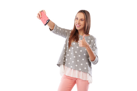 Mid shot of happy girl taking selfie and showing ok gesture. Using smartphone isolated on a white background Stock Photo