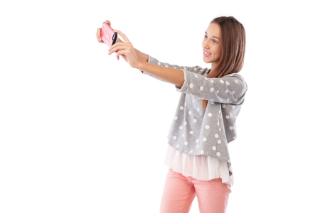 pullover: Mid side view of cute girl making selfie photo via smartphone isolated on a white background. Smiling and posing at the camera. Girl tries to make a good shot Stock Photo