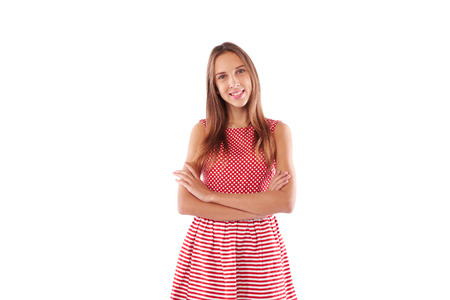 folding arms: Mid portrait of smiling girl. Folding arms while posing at the camera. Looking confident and satisfied. She wears cute drees in white and red colors