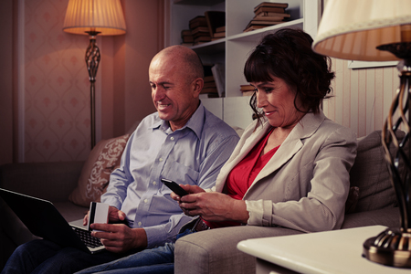 side shot: A mid side shot of smiling people sitting on the brown settee surrounded by lamps and booksettle. Man with laptop laughing and riant lady looking at her mobile Stock Photo