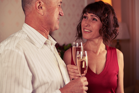 Close-up of harmonious couple looking deeply at each other, holding two champagne flutes clink glasses at the home Stock Photo
