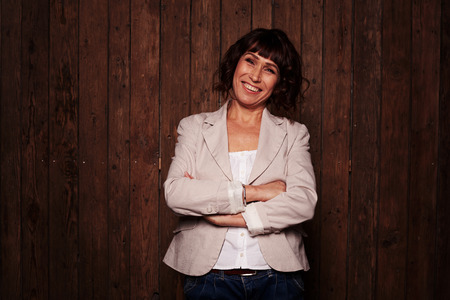 A mid shot of beautiful smiling chestnut female standing against the brown wooden background, wearing dark blue jeans, white blouse and light blazer. Lady folding arms, having riant eyes and cute smile
