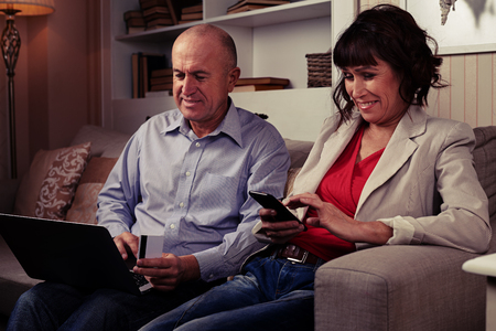 side shot: A mid side shot of an elderly pair on the couch, smiling and looking at gadgets. Man in blue shirt holding a card and female in red blouse and light stripped blazer Stock Photo