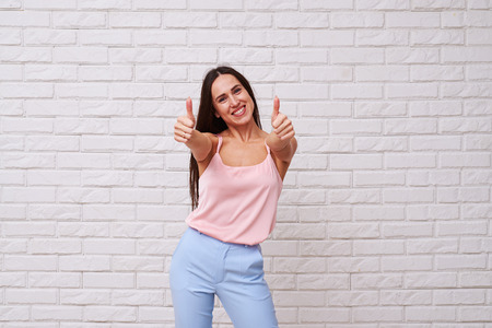 exhilarating: Mid shot of exhilarating woman posing with two thumbs up. Looking at the camera. Beautiful longhaired woman wearing nice well-combined suite