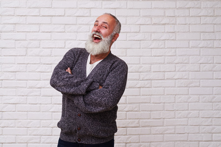 folding arms: A mid shot of an attractive beard male standing confidently and folding his arms on the chest. Man dressed in grey wooly sweater