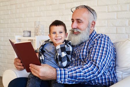 kid book: A mid shot of cute grandpa and his grandchild reading a book. Man wearing a shirt and kid with blue eyes Stock Photo