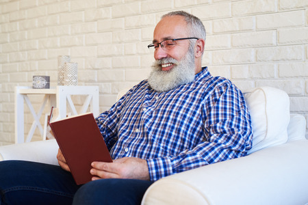 side shot: A mid side shot of smiling beard man reading a book. Male sitting in the soft armchair, wearing shirt and jeans