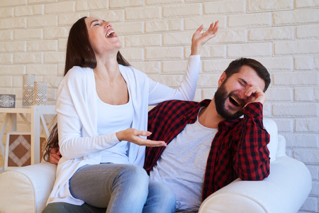 dearest: Mid shot of humorous pair laughing at a joke, sitting in the living room in an armchair. Couple at home in living room