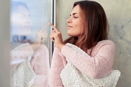 rosy: Close-up of charming girl in rosy sweater. Sitting by the window and embracing a lace pillow. Pretty girl with natural makeup, rosy lips resting at home Stock Photo