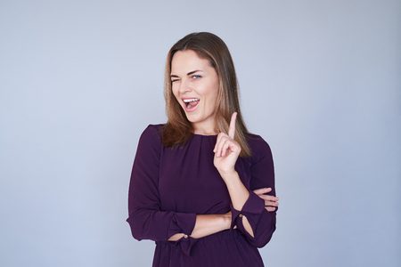 Close-up of joyful woman winking when pointing an index finger over white background. Looking at the camera. Folded arms; soft look