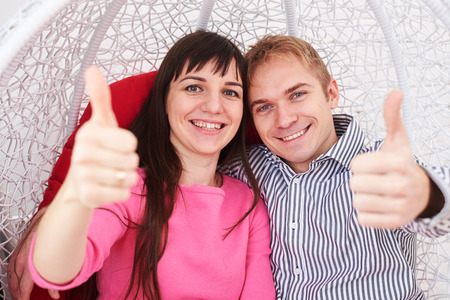 familia abrazo: Close-up of excited married couple holding thumbs up while posing at the camera. Sitting in the winging hanging chair Foto de archivo