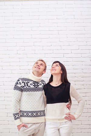 looking upwards: Mid-length shot of pleased young couple thinking and looking upwards into the copy space