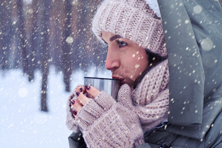 to get warm: Side view of pensive woman holding a cup of coffee. Woman with a cup of hot tea in winter walk. Concentrated woman holding a cup with a hot tea while looking at the distance