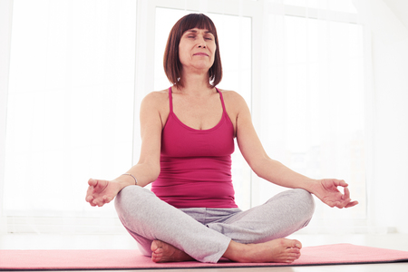 Mid low angle shot of sporty woman practicing yoga in the gym. Sitting on a yoga mat. Crossing legs and holding hands. Calmness and relax, woman happiness