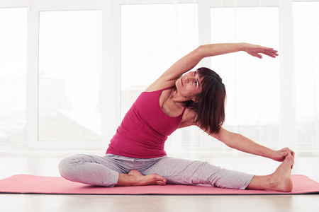 congenial: Mid shot оf congenial cheerful athlete stretches in a half-bound ankle pose. Beautiful young woman wearing sport clothing enjoying yoga indoors