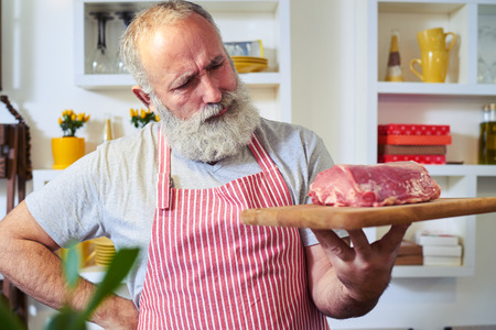 Mid shot of man holding a cutting board with steaks on it. Thinking what to prepare. Male wearing a stripped red and white apron standing in the kitchen