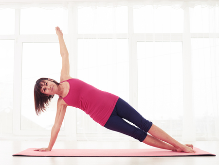 Mid shot of mature brunette practices yoga side plank pose in the gym. Woman dressed in sportswear practising yoga workout in the gym on the yoga mat