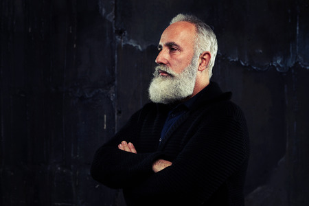 narrowly: A mid shot from the side of a well-built man with grey beard and folded arms looking narrowly. Male dressed in warm sweater Stock Photo