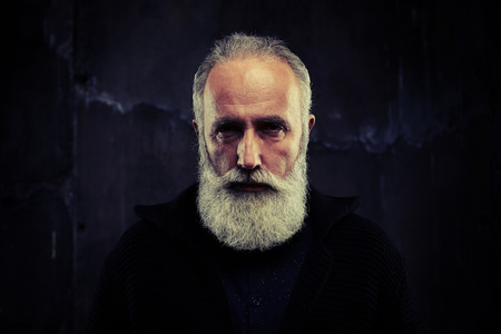 knitted jacket: A mid shot of an elderly handsome grey bearded man looking narrowly into the lens. Male wearing black knitted jacket and a blue shirt Stock Photo