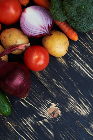displaced: High angle of collection of picked vegetables displaced over black background. Healthy eating background studio photography of different and vegetables isolated on dark flat layout