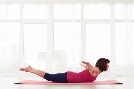 bhujangasana: Side view of woman involving into yoga asana bhujangasana cobra pose. The concept of fitness and health care. Strengthening the back and opening the chest