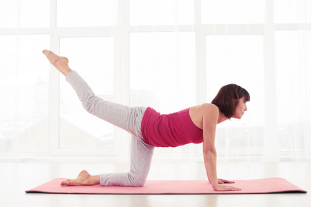 mature women only: Doing balance exercise, kneeling opposite. Woman performing exercise to control balance. Calmness and relax. The concept of harmony between body and spirit