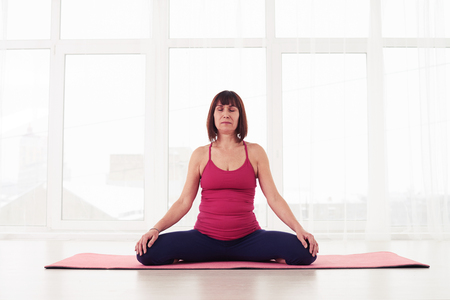 yogini: Mid shot of yogini relaxing and meditating during yoga class in a gym. Portrait of a beautiful woman sitting in yoga pose at the gym. Meditating and doing yoga alone Stock Photo