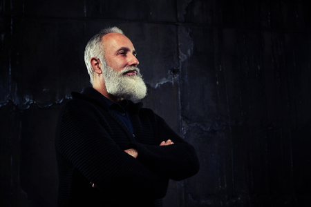 narrowly: A mid left side-view shot of elderly man with beard, having his arms folded and smiling. Man wearing black jacket Stock Photo