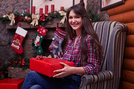 festively: Side view shot of delighted lady before opening the gift sitting in an armchair with a background of a festively Christmas stockings hang on decorated fireplace