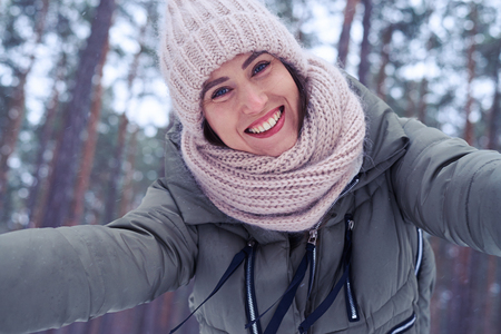 Low angle of merry female smiling at the camera spreading two hands. Model wearing padded jacket with knitted scarf and mittens Stock Photo