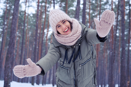 young lady: Low angle of smiling woman posing at the camera. Woman in coat showing pink knitted mittens against snowy forest. Outdoors shot of young lady enjoying nice day in the forest