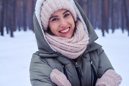 Close-up of the young pretty woman looks at the camera slightly having inclined a head. Model wearing padded jacket with knitted scarf and mittens. Posing at the camera Stock Photo