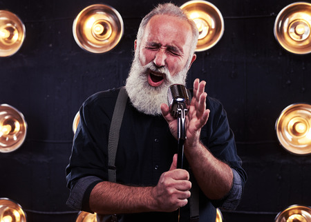nudo maschile: Close-up of impassioned man singing in a silver vintage microphone wearing dark shirt and suspenders. Using studio microphone and posing at the camera