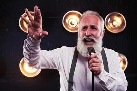 nudo maschile: Primo piano di uomo emotivo in camicia bianca e bretelle in possesso di un microfono da studio retrò argento su sfondo di riflettori sfocate Archivio Fotografico