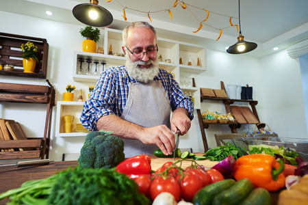 Low angle of smiling bearded man in a good mood preparing food for the dinner. Stock Photo