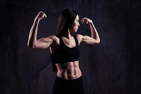 Close-up shot of woman flexing muscles showing great relief of arms and torso while exercising against rough dark wall with rusty gears