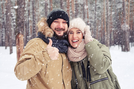 exhilarated: Close-up of exhilarated husband with thumb up hugging wife during the snowfall in the forest.
