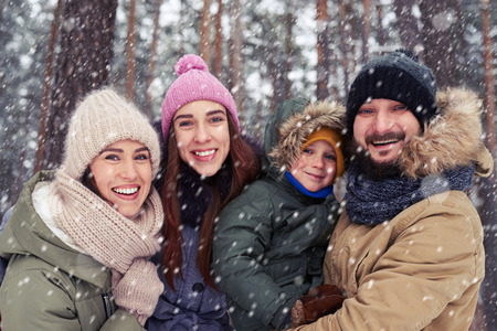 couple outdoor: Low angle of extremely happy family having fun on a cold winter day.