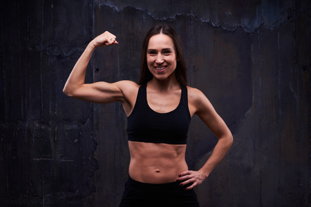 only the biceps: Close-up of fitness sporty girl showing her well trained biceps against black background. Stock Photo