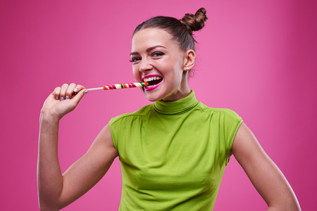 exhilarated: Exhilarated girl tasting a lollipop on a stick isolated over pink background.