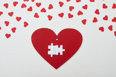 interlocked: High angle of two white interlocked puzzle pieces over red heart isolated on white background Stock Photo