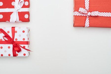 rea: High angle of dotted rea and white gift boxes with copy space. Present boxes for gifts covered with wrapping paper