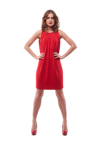 woman surprise: Full-length shot of young woman in red dress with hands on hips standing isolated against white background Stock Photo